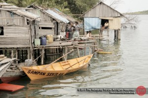 "The school boat outside the homes of ""anak laut"", the sea tribe children."